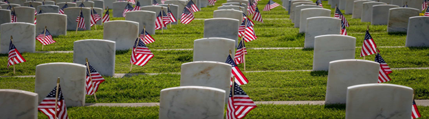 Rows of grave markers of servicemen and women are decorated with American flags for Memorial Day. Dallasgolden/Istock via Getty Images